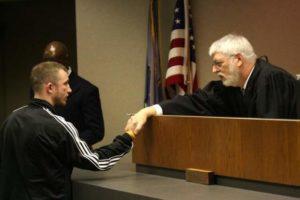 Judge MacKenzie congratulating a gradute